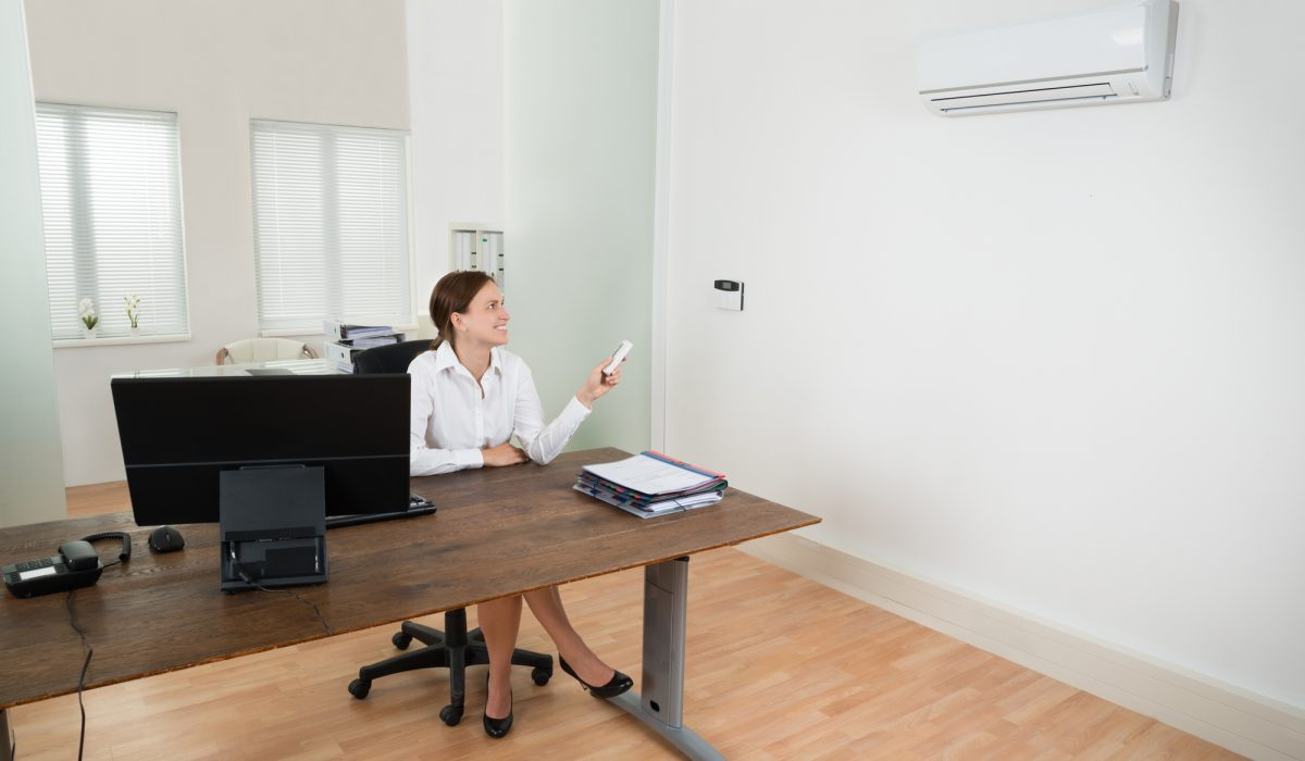 Happy Businesswoman Operating Air Conditioner With Remote Control In Office